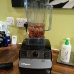 A blender on a kitchen surface with almonds and water in it.